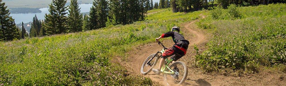 Biker going down hill on mountain trail