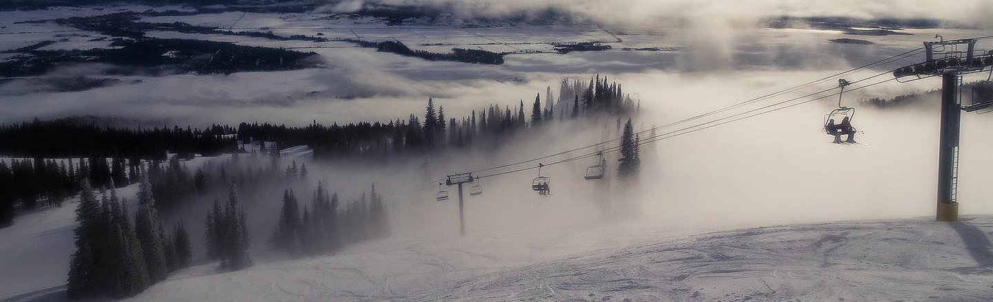 Ski lifts ascending the misty mountain
