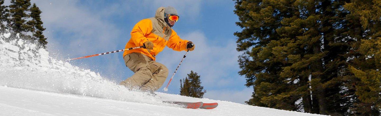 Skiier in orange jacket going down the slope